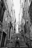 Junger Mann, der auf Schritte in der alten Stadt sitzt Stockbild