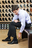 Junger Mann, der auf Schuhen versucht stockbilder