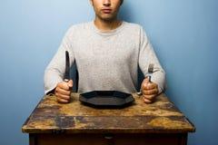 Junger Mann, der auf sein Abendessen wartet Stockfoto
