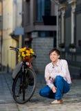 Junger Mann, der auf sein Datum nahe einem Fahrrad wartet stockfoto