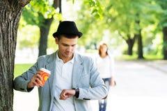 Junger Mann, der auf seine Liebe im Park überprüft die Uhr wartet Stockfotografie