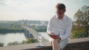 Junger Mann, der auf seiner Tablette in der tiefen Konzentration bei der Stellung auf einer Brücke mit der Sonneneinstellung hint stock video footage