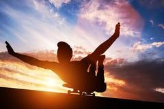 Junger Mann, der auf Skateboard bei Sonnenuntergang liegt Stockbild