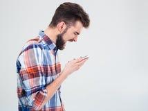 Junger Mann, der auf Smartphone schreit Lizenzfreie Stockfotos
