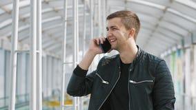 Junger Mann, der auf Smartphone spricht stockfotografie