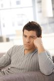 Junger Mann, der auf Sofa denkt Stockfotografie