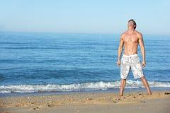 Junger Mann, der auf Sommer-Strand steht Lizenzfreie Stockbilder