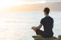 Junger Mann, der auf Spitzenozeanklippe während des Sonnenuntergangs meditiert stockfoto