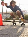 Junger Mann, der auf städtische Straße Skateboard fährt Stockfotos