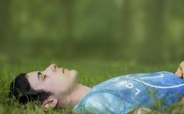Junger Mann, der auf stille Art auf Gras legt Lizenzfreie Stockbilder