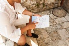 Junger Mann, der auf Straße sitzt und auf Karte zeigt Lizenzfreies Stockbild