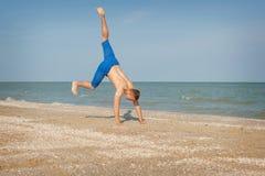 Junger Mann, der auf Strand springt Lizenzfreie Stockbilder