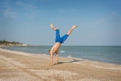 Junger Mann, der auf Strand springt Stockfotos