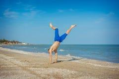 Junger Mann, der auf Strand springt Stockfoto