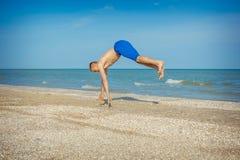 Junger Mann, der auf Strand springt Lizenzfreies Stockbild