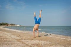 Junger Mann, der auf Strand springt Lizenzfreies Stockfoto
