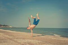 Junger Mann, der auf Strand springt Stockbilder