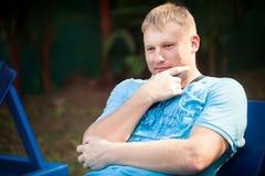 Junger Mann, der auf sunbed sitzt Stockbild