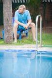 Junger Mann, der auf sunbed sitzt Stockfotografie