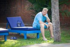 Junger Mann, der auf sunbed sitzt Stockbilder