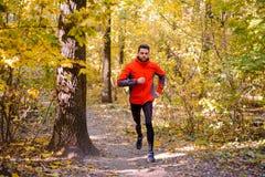 Junger Mann, der auf Sunny Trail in schönen Autumn Oak Forest läuft Stockfoto