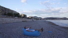 Junger Mann, der auf Treffpunktsofa aufbläst und sich hinlegt, um Rest auf Seestrand zu genießen stock video