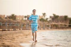 Junger Mann, der auf tropischem Erholungsort rüttelt Stockfotografie