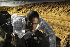 Junger Mann, der auf Wüstenfelsen kriecht lizenzfreie stockfotografie