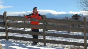 Junger Mann, der auf Zaun an einem schönen Wintertag an der Landschaft lächelt und sich lehnt stock video footage