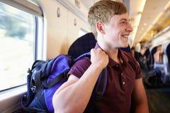 Junger Mann, der auf Zug-Reise sich entspannt Lizenzfreies Stockfoto