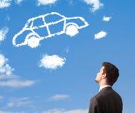 junger Mann, der Autowolke auf einem blauen Himmel betrachtet Lizenzfreie Stockfotos
