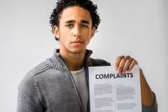 Junger Mann, der Beanstandungsbericht hält stockbilder