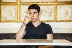 Junger Mann, der bei Tisch sitzt, Nase auswählend Stockfotografie
