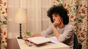 junger Mann, der beim Studieren gebohrt erhält stock footage