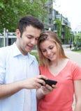 Junger Mann, der Bilder an seinem Telefon zeigt Stockbild