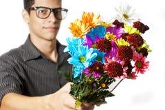 Junger Mann, der Blumen gibt Lizenzfreie Stockfotografie