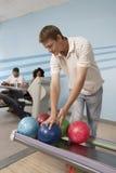 Junger Mann an der Bowlingbahn, die Ball wählt Lizenzfreies Stockfoto