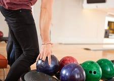 Junger Mann, der Bowlingkugel vom Gestell wählt Stockbilder