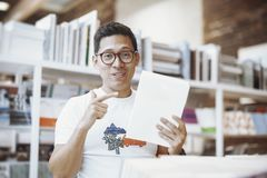 Junger Mann, der Buch mit Blinddeckel hält und es zu einem Zuschauer demonstriert Lizenzfreies Stockbild