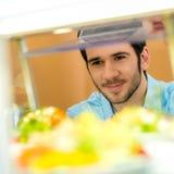 Junger Mann der Cafeterianahrungsmittelbildschirmanzeige wählen Salat lizenzfreie stockfotografie