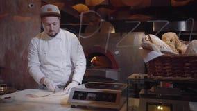 Junger Mann in der Chefuniform, die rohe Fische auf Schneidebrett schneidet Kochen Sie das Trennen des Fischfilets von den Knoche stock video footage