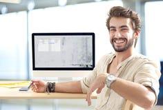 Junger Mann, der an Computer arbeitet Lizenzfreie Stockfotos