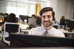 Junger Mann, der am Computer mit Kopfhörer im beschäftigten Büro arbeitet stockfotografie