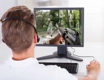 Junger Mann, der Computer-Spiele spielt Stockbilder