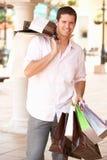 Junger Mann, der das Einkaufen genießt Stockbild