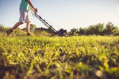 Junger Mann, der das Gras mäht Stockfoto