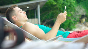 Junger Mann, der das intelligente Telefon liegt im Klappstuhl auf Strand verwendet Stockfotografie