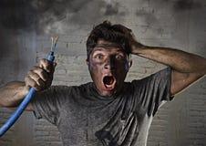 Junger Mann, der das Kabel raucht nach elektrischem Unfall mit schmutzigem gebranntem Gesicht im lustigen traurigen Ausdruck hält Lizenzfreie Stockfotografie