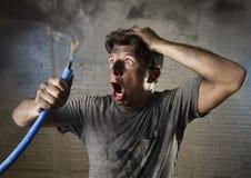 Junger Mann, der das Kabel raucht nach elektrischem Unfall mit schmutzigem gebranntem Gesicht im lustigen traurigen Ausdruck hält Stockfoto