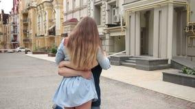 Junger Mann, der das Mädchen fest hält ihre Taille wirbelt
